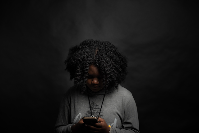 Woman looking at her phone in a dark room, checking social media channels