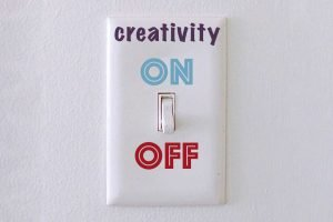 Light switch on a wall, labelled Creativity on and off