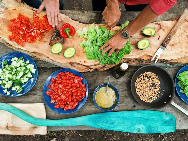 Overhead shot of two people preparing a salad, chopping lettuce, tomatoes, cucumbers and avocados