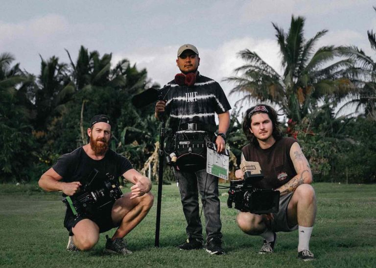 Two cameramen and a sandman posing on a lawn in front of some trees