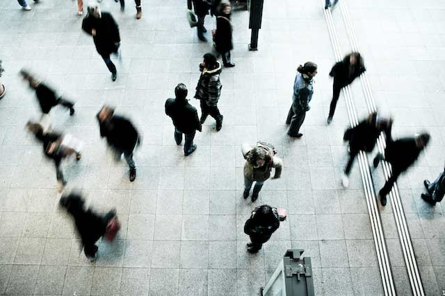 Overhead view of a train station concourse with many different types of people