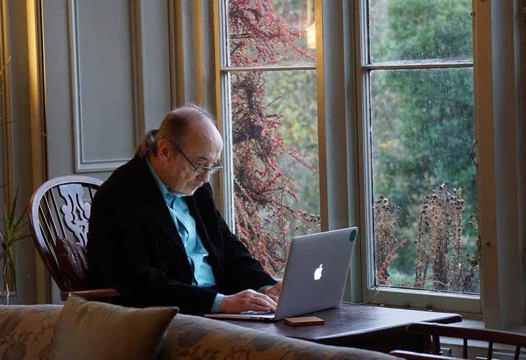 Older man sitting by a window using a macbook