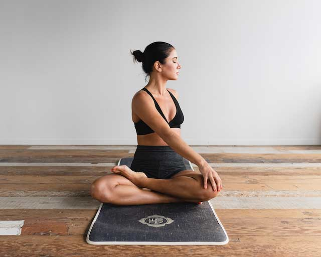 Woman in exercise gear sitting cross legged on a yoga mat and twisting to one side