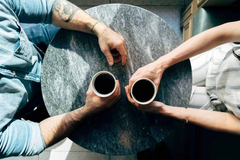 Two people sitting at a table with coffee cups in front of them having a conversation