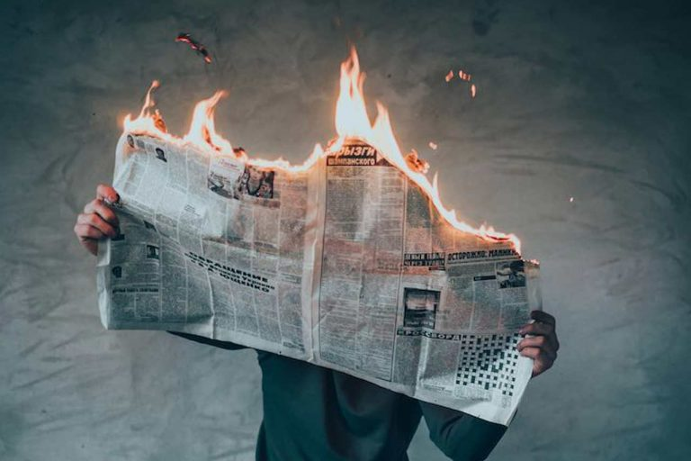 Man calmly reading a newspaper while it's on fire