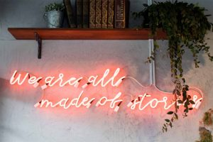 A neon on a white wall saying we are all made of stories