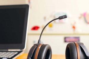 Customer service headset sitting on a desk next to a laptop